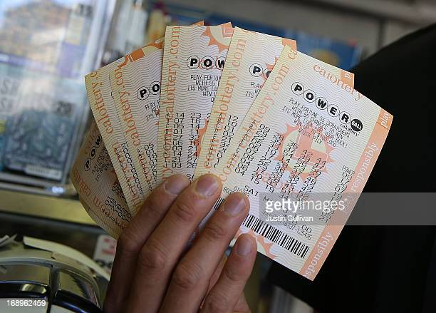 A customer holds $140 worth of Powerball tickets that he just purchased on May 17 2013 in San Francisco California People are lining up to purchase...
