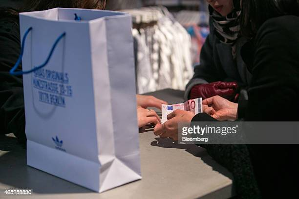 A customer holds a 10 euro banknote as they make a purchase at the payment counter inside an Adidas AG Originals store in Berlin Germany on Wednesday...
