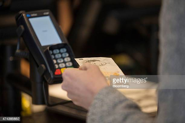 A customer holds a 10 pound British banknote next to a Verifone Systems Inc credit card payment device at a restaurant in London UK on Friday May 22...