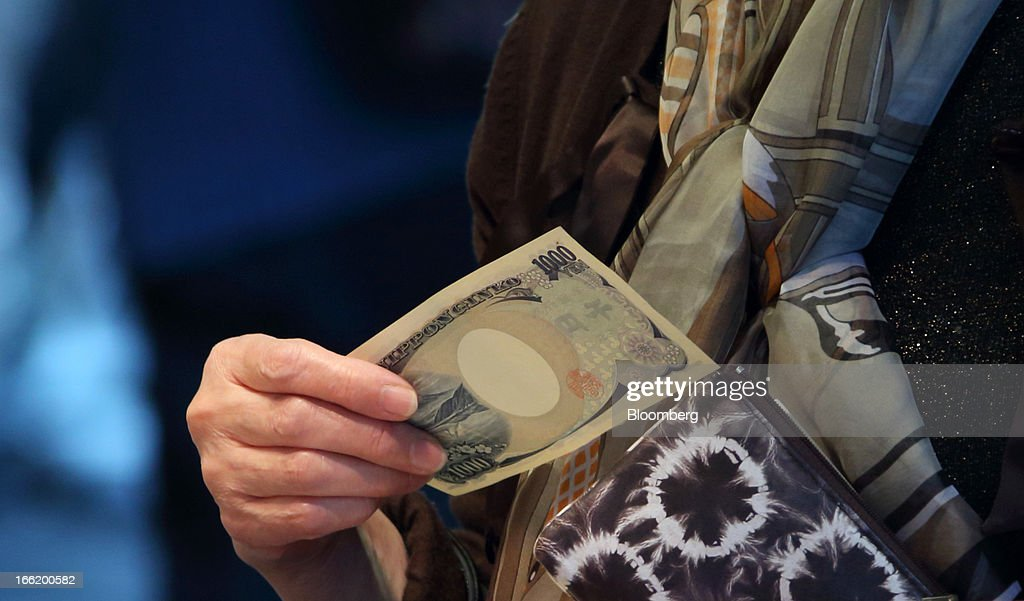 A customer holds a 1,000 yen bank note at a supermarket in Tokyo, Japan, on Tuesday, April 9, 2013. After Bank of Japan Governor Haruhiko Kuroda's first policy meeting as governor on April 4, the central bank set a two-year horizon for the 2 percent annual price-increase target that it adopted in January at the urging of Prime Minister Shinzo Abe. Photographer: Tomohiro Ohsumi/Bloomberg via Getty Images