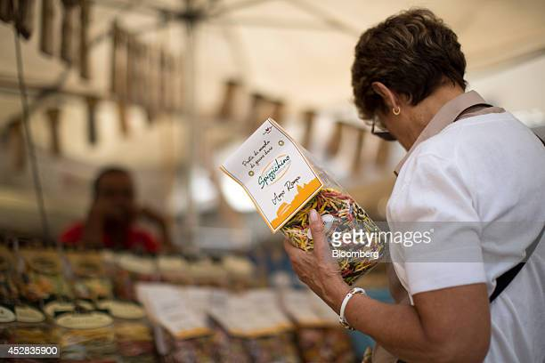 A customer holds a bag of multicolored dried pasta while browsing a street stall at the Campo de Fiori outdoor market in Rome Italy on Saturday July...