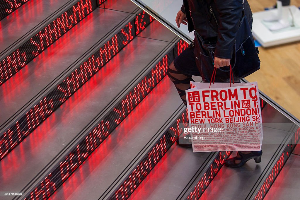 A customer holds a branded paper carrier bag as she walks up an illuminated staircase inside a Uniqlo store the fashion clothing retailer operated by...