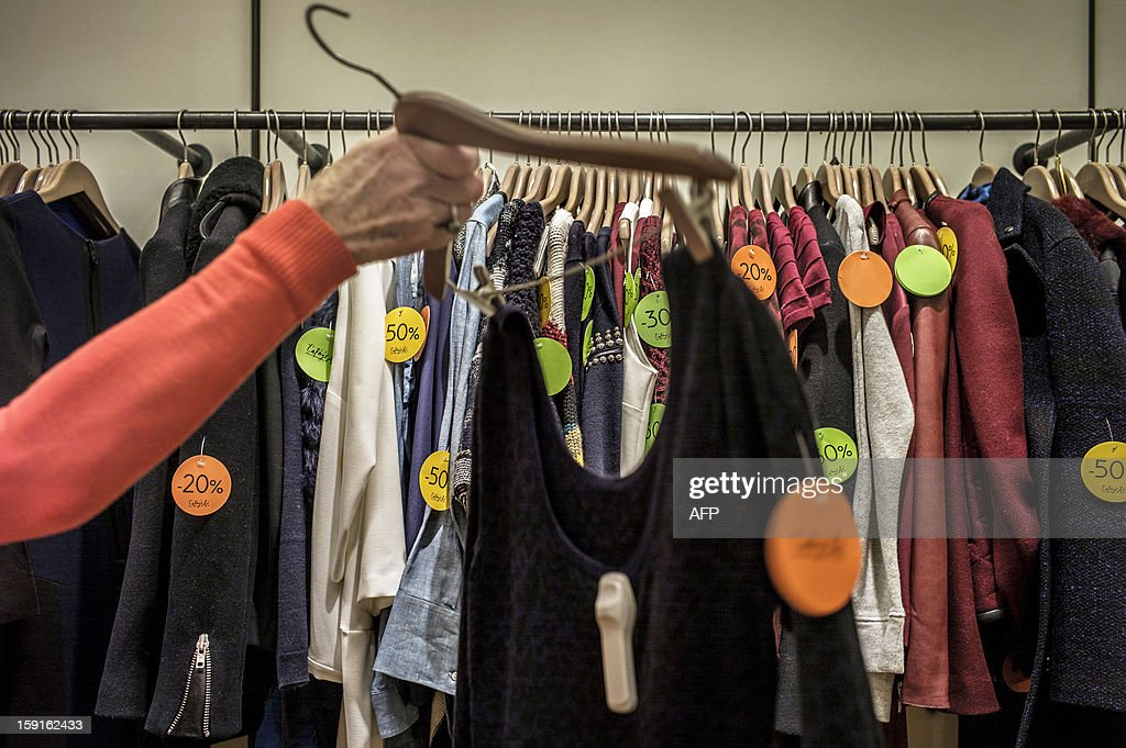 A customer holds a clothes rack as she browses clothes at the Galeries Lafayette department store in Lyon, on January 9, 2013, during the official start of winter sales. AFP PHOTO / JEFF PACHOUD