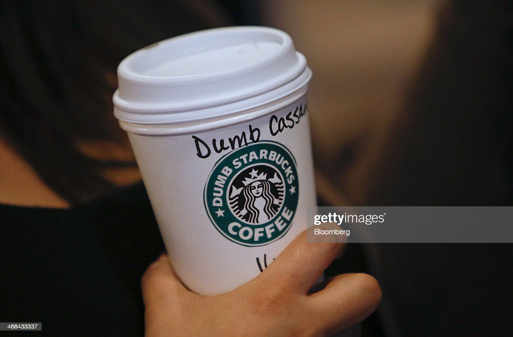A customer holds a coffee cup at the Dumb Starbucks Coffee store, a parody of the Starbucks Corp. coffee chain, in Los Angeles, California, U.S., on Monday, Feb. 10, 2014. Dumb Starbucks, which opened this past weekend, offered Dumb Vanilla Blonde Roast, Dumb Chai Tea Latte, and Dumb Caramel Macchiato, all available in sizes Dumb Venti, Dumb Grande, and Dumb Tall. Photographer: Patrick T. Fallon/Bloomberg via Getty Images