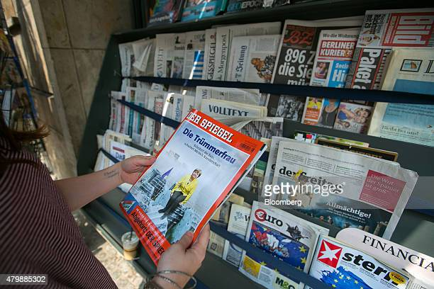 A customer holds a copy of weekly news magazine Der Spiegel featuring a photo montage of Angela Merkel Germany's chancellor sitting on Greek ruins to...