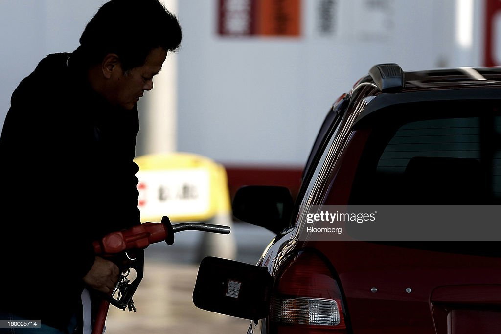 A customer holds a fuel pump ready to fill the tank of a vehicle at a self service gas station in Soka City, Saitama Prefecture, Japan, on Friday, Jan. 25, 2013. Japan's consumer prices fell for the seventh time in eight months, underscoring the risk that the central bank may struggle to reach a 2 percent inflation target unless it implements new easing measures earlier than planned. Photographer: Kiyoshi Ota/Bloomberg via Getty Images