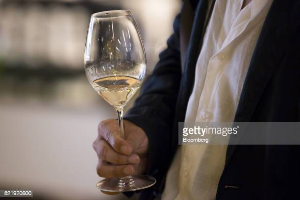 A customer holds a glass of sparkling sake at the Japan Awasake Association booth during a Sake Marche event at the Isetan Shinjuku department store...
