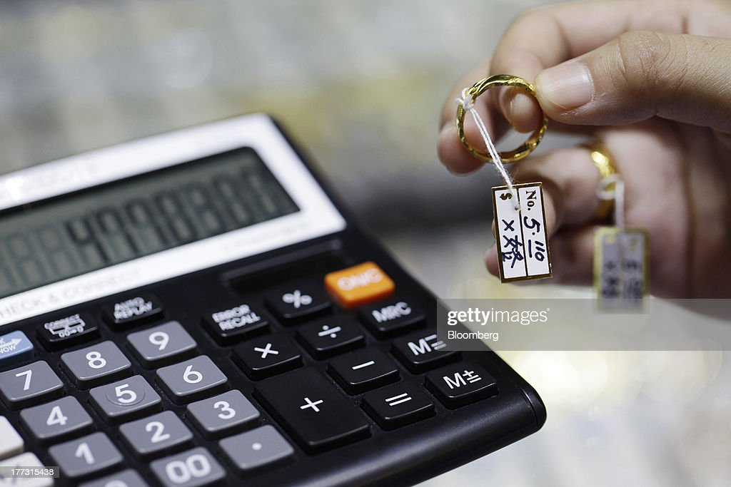 A customer holds a gold ring for a photograph while calculating prices at a jewelry store in Jakarta, Indonesia, on Thursday, Aug. 22, 2013. Gold jewelry demand in Indonesia is set to expand to a four-year high as consumers in Southeast Asia's biggest buyer join India to China in increasing purchases as prices slump and the middle class expands. Photographer: Dimas Ardian/Bloomberg via Getty Images