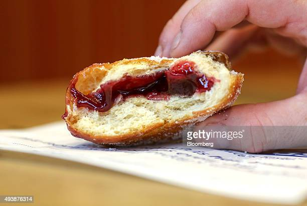 A customer holds a half finished jam doughnut inside a Greggs Plc sandwich chain outlet in Caterham UK on Thursday Oct 22 2015 Samestore sales at...