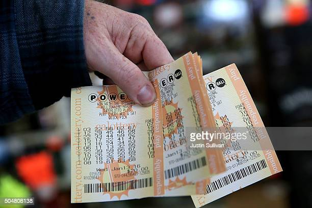 A customer holds a handful of Powerball tickets at Kavanagh Liquors on January 13 2016 in San Lorenzo California Dozens of people lined up outside of...