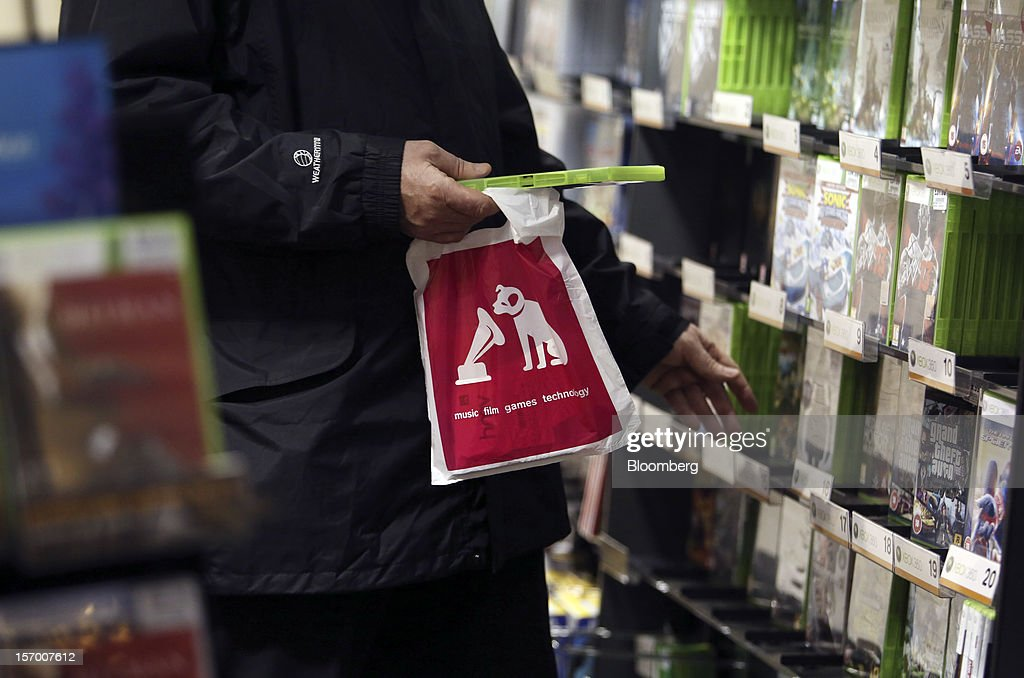 A customer holds a HMV-branded shopping bag whilst browsing the video games section inside a HMV pop-up store in London, U.K., on Tuesday, Nov. 27, 2012. Fashion chain Hobbs is among those that have opened pop-up stores for the first time this year, while CD and DVD retailer HMV Group Plc is adding more than usual for the holiday in an effort to win business. Photographer: Chris Ratcliffe/Bloomberg via Getty Images