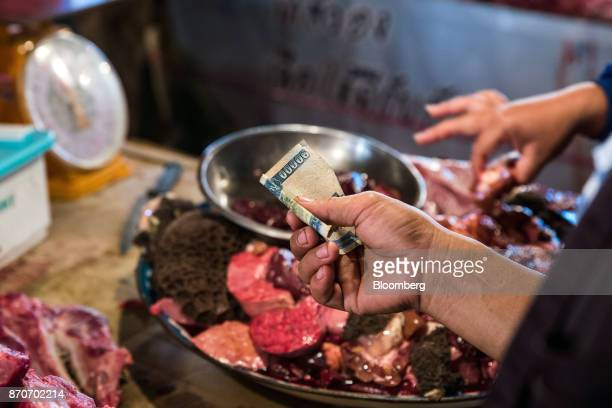 A customer holds a Laotian 10000 Kip banknote at a butcher's store in Vientiane Laos on Thursday Nov 2 2017 Located in the Mekong region Southeast...