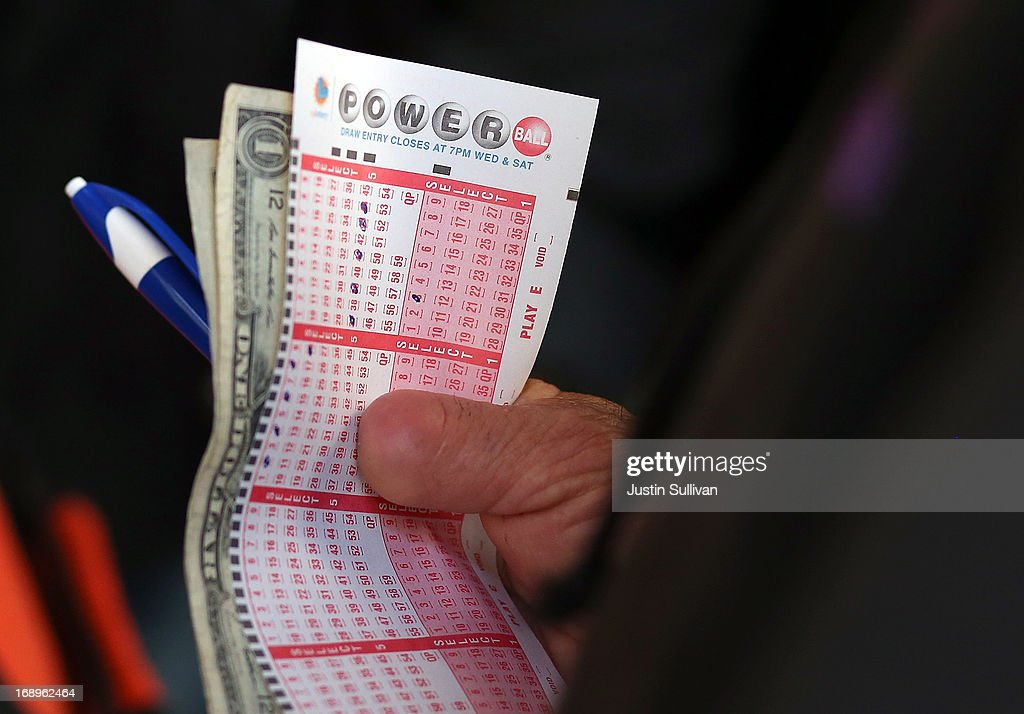 A customer holds a Powerball ticket and money as he waits in line on May 17, 2013 in San Francisco, California. People are lining up to purchase $2 Powerball tickets as the multi-state jackpot hits $600 million.
