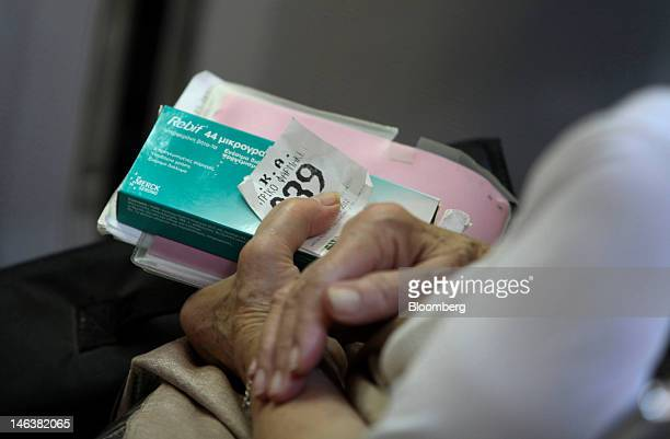 A customer holds a service ticket and prescription drugs while waiting inside a pharmacy in Athens Greece on Friday June 15 2012 Greeks head to the...