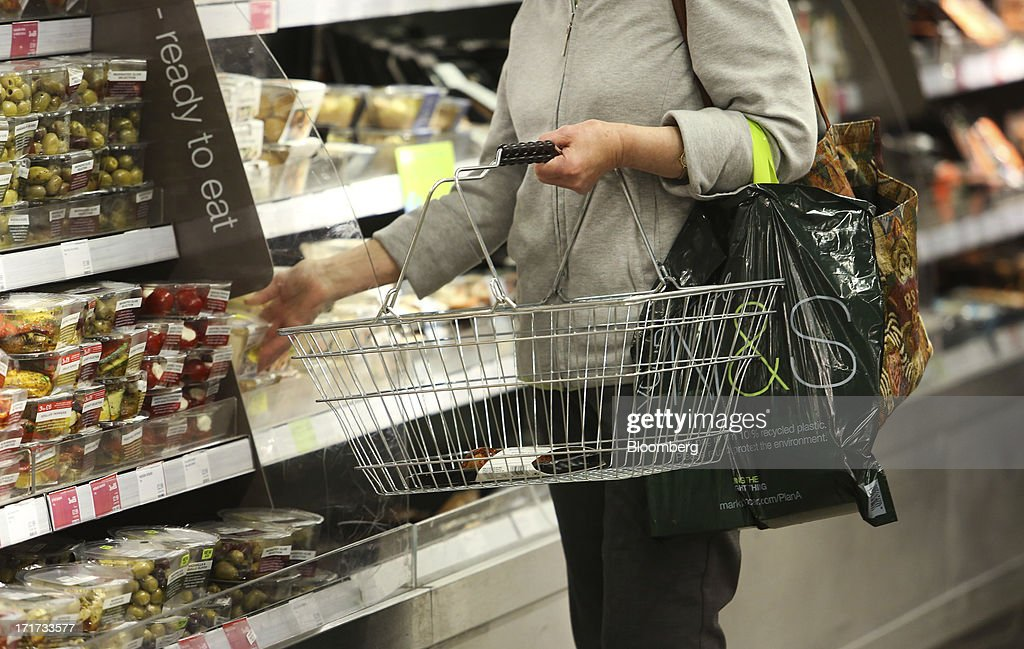 A customer holds a shopping basket as she selects an item inside a Marks & Spencer Group Plc (M&S) food hall in the Westfield Stratford City retail complex in London, U.K., on Thursday, June 27, 2013. U.K. retail sales rose more than economists forecast in May as consumers spent more online and food sales increased at their fastest pace for more than two years. Photographer: Chris Ratcliffe/Bloomberg via Getty Images