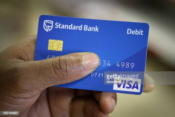 A customer holds a Standard Bank Group Ltd visa debit card used for transactions at access points serving MPesa mobile phone money transfers in...