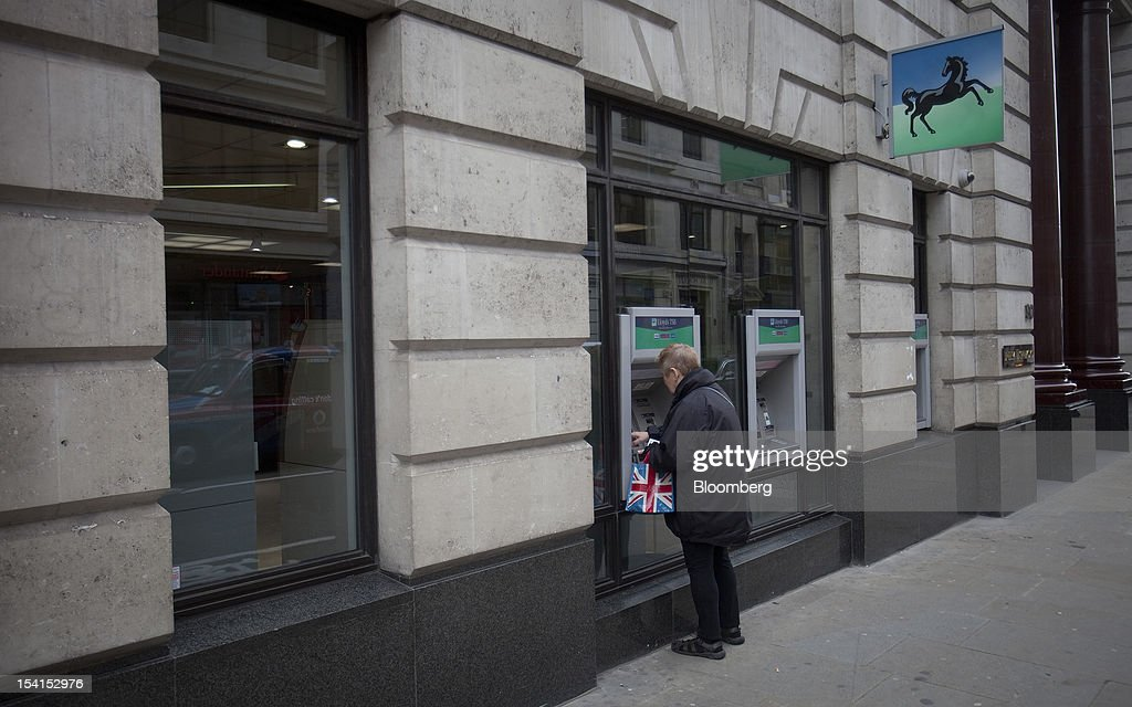 A customer holds a Union Jack bag as she uses an automated teller machine (ATM) outside a Lloyds TSB bank branch, part of the Lloyds Banking Group Plc, in London, U.K., on Monday, Oct. 15, 2012. U.S. homeowners filed a lawsuit against 12 banks, including Lloyds Banking Group Plc, Barclays Bank Plc, and JPMorgan Chase & Co., claiming that manipulation of the benchmark Libor lending rate made their mortgage repayments more expensive. Photographer: Simon Dawson/Bloomberg via Getty Images