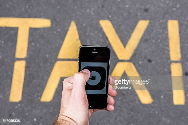 A customer holds an Apple Inc iPhone displaying the Uber Technologies Inc car service application logo in front of a taxi rank road marking in this...