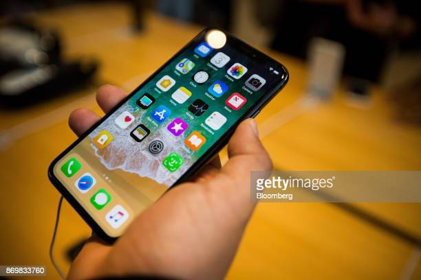 A customer holds an Apple Inc iPhone X smartphone during the sales launch at a store in New York US on Friday Nov 3 2017 The $1000 price tag on Apple...