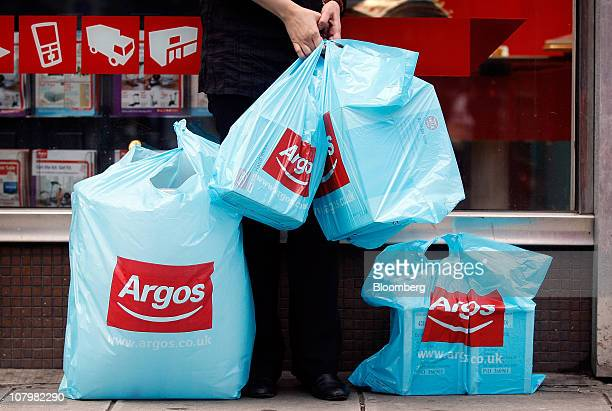 A customer holds branded shopping bags outside an Argos store operated by Home Retail Group Plc in London UK on Tuesday Jan 11 2011 UK retail sales...