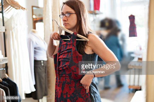Customer holds dress against her in shop : Stock Photo