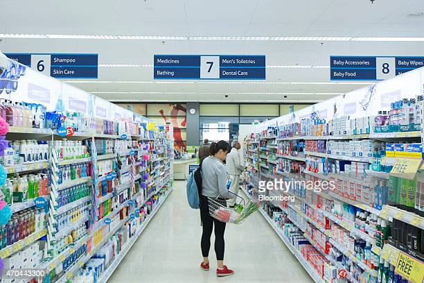 A customer holds her goods in a shopping basket as she browses goods displayed in the toiletries and dental care aisle inside a Tesco supermarket...