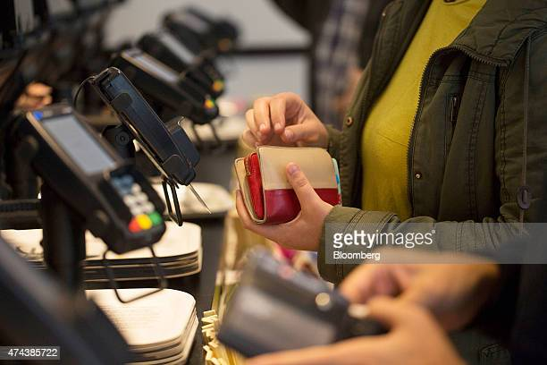 A customer holds her purse while making a purchase using a debit card via a Verifone Systems Inc payment device at a restaurant in London UK on...