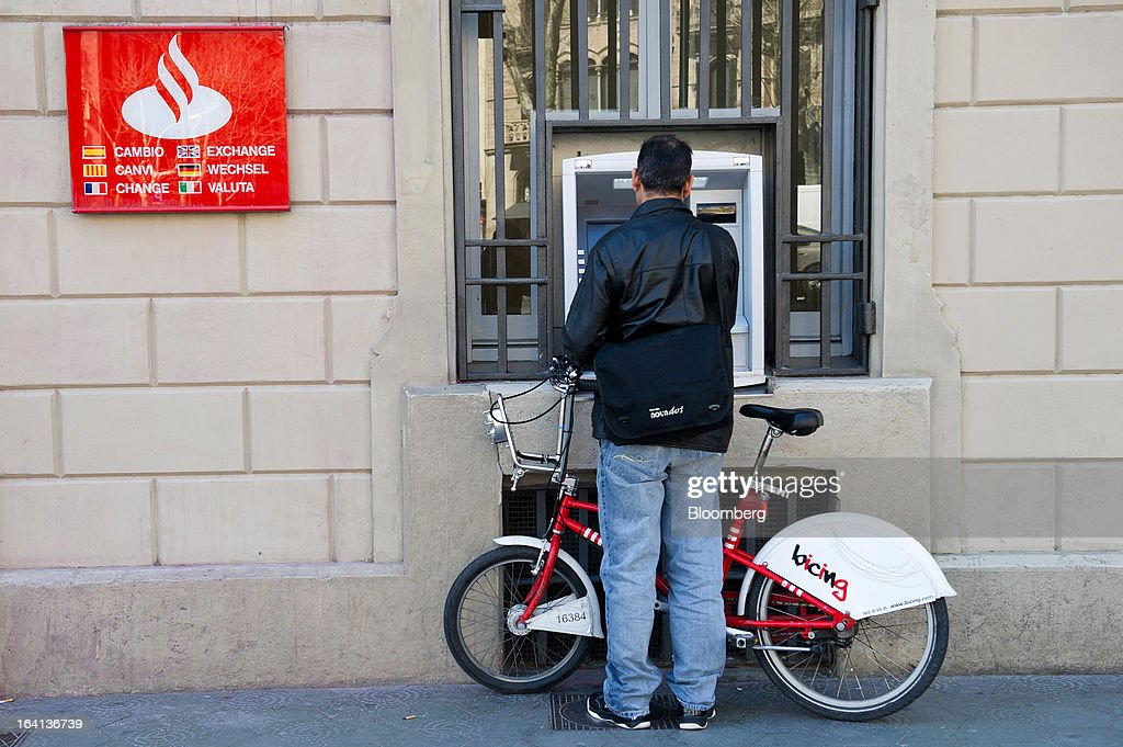 A customer holds his Bicing city bike while using an automated teller machine (ATM) outside a Banco Santander SA branch in Barcelona, Spain, on Wednesday, March 20, 2013. Officials from the troika of international creditors -- the ECB, the International Monetary Fund and the European Commission -- are in Cyprus discussing further capital controls and possibly extending a bank holiday to the end of the week, a European official familiar with the talks said on condition of anonymity because the discussions are confidential. Photographer: David Ramos/Bloomberg via Getty Images