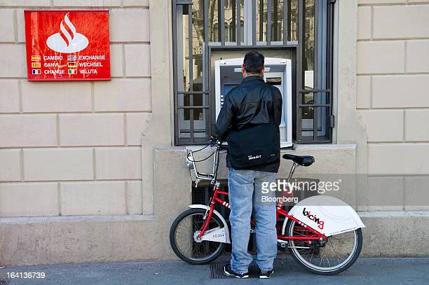 A customer holds his Bicing city bike while using an automated teller machine outside a Banco Santander SA branch in Barcelona Spain on Wednesday...