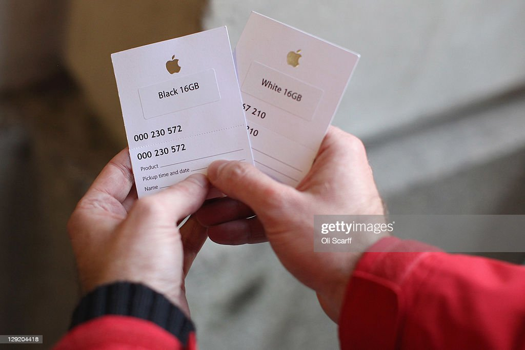 A customer holds his queue-cards as he waits outside the Apple store in Covent Garden to buy an iPhone 4S on October 14, 2011 in London, England. The widely anticipated new mobile phone from Apple has seen customers queue in cities around the world for hours to be amongst the first to buy the device.