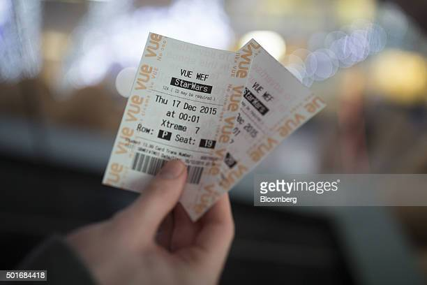 A customer holds his tickets to view the first public screening of Walt Disney Co's 'Star Wars The Force Awakens' at a Vue Entertainment Ltd cinema...