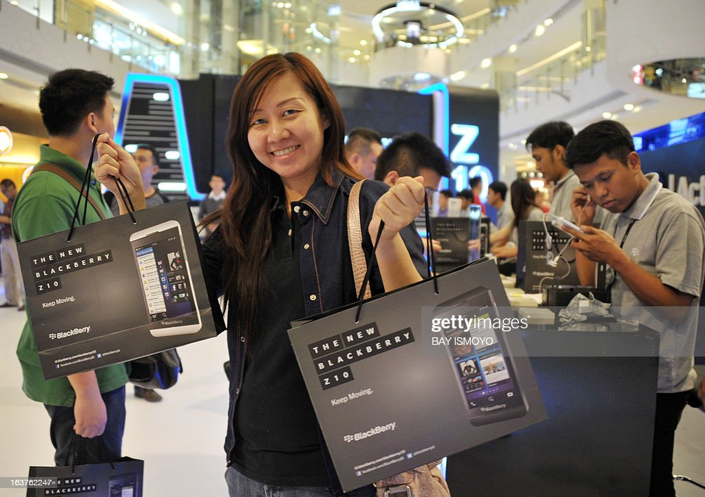 A customer holds new Blackberry Z10 phones, bought at the BlackBerry launch event at a shopping mall in Jakarta on March 15, 2013. BlackBerry launched its new Z10 smartphone in Indonesia, the company's third-largest market as it rapidly loses ground elsewhere to rivals such as Apple and Samsung. AFP PHOTO / Bay ISMOYO