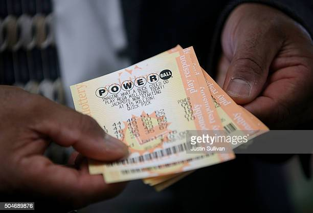 A customer holds Powerball tickets that he purchased at Kavanagh Liquors on January 12 2015 in San Lorenzo California Dozens of people lined up...