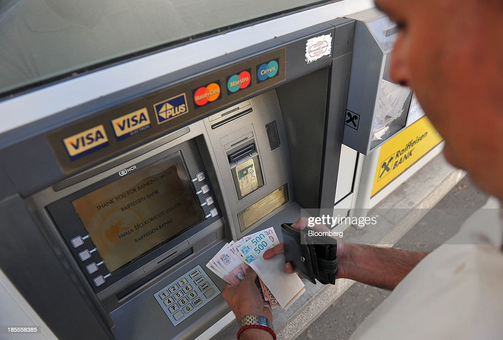A customer holds Serbian dinar notes alongside an automated teller machine (ATM) operated by Raiffeisen Bank International AG, in this arranged photograph in Belgrade, Serbia, on Monday, Oct. 21, 2013. Serbia's government revealed a salvo of measures to bring the public finance deficit and debt back under control by 2017 after the head of the largest coalition party warned the country was on the brink of insolvency. Photographer: Oliver Bunic/Bloomberg via Getty Images