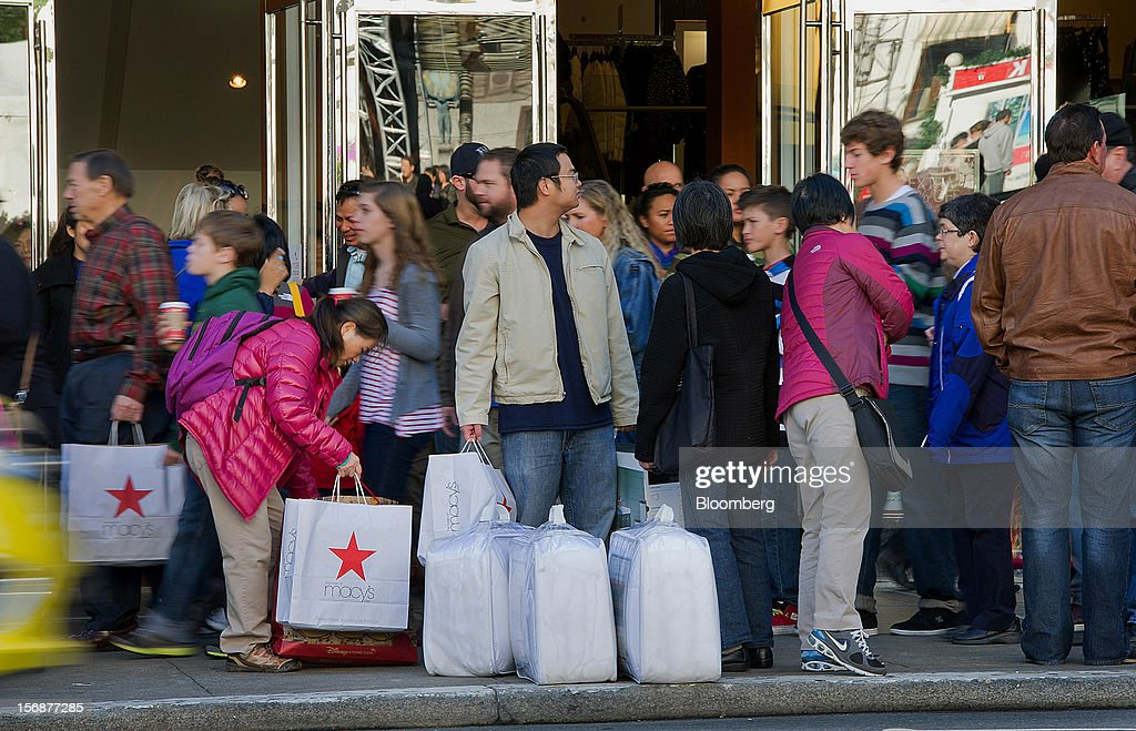 A customer holds shopping bags outside of the Westfield San Francisco Centre in San Francisco, California, U.S., on Friday, Nov. 23, 2012. To get shoppers to spend more than last year, retailers have continued to turn Black Friday, originally a one-day event after Thanksgiving, into a week's worth of deals and discounts. Photographer: David Paul Morris/Bloomberg via Getty Images