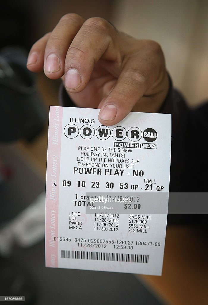 A customer holds up a Powerball lottery ticket at a 7-Eleven store on November 28, 2012 in Chicago, Illinois. Jim Bayci, who owns the store, estimates more than half of his customers included at least one Powerball ticket with their purchase today. The jackpot for Wednesday's Powerball drawing is currently at $550 million which is the richest Powerball pot ever. It is likely to rise even more as people continue to buy before tonights drawing.