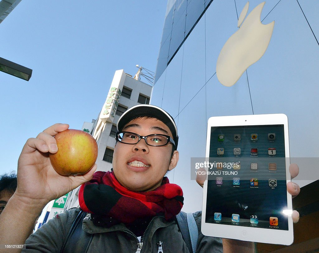A customer holds up an apple after he purchased Apple's new 7-inch sized 'iPad mini' tablet (R) at an Apple store in Tokyo on November 2, 2012. The iPad mini made its debut as Apple takes on rivals Amazon, Google and Samsung with a smaller version of its coveted tablet computer, but it was a low-key start as sales began in Japan. AFP PHOTO / Yoshikazu TSUNO