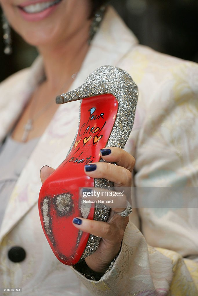 A customer holds up her newly autographed Christian Louboutin shoe at the launch of his new fall collection at Barneys New York on May 7, 2008 in Beverly Hills, California.