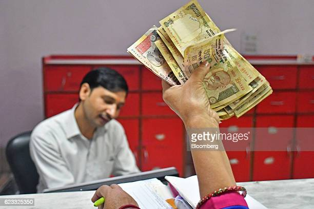 A customer holds up Indian five hundred and one thousand rupee banknotes while waiting to exchange the bills at an India Post branch in New Delhi...