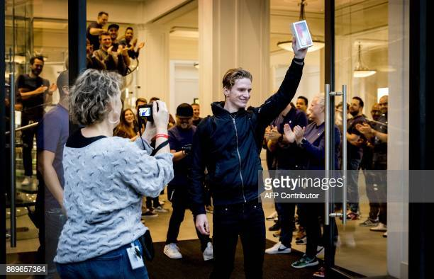 A customer holds up the new iPhone X outside an Apple store in Amsterdam during the launch of the new iPhone X on November 3 2017 / AFP PHOTO / ANP /...
