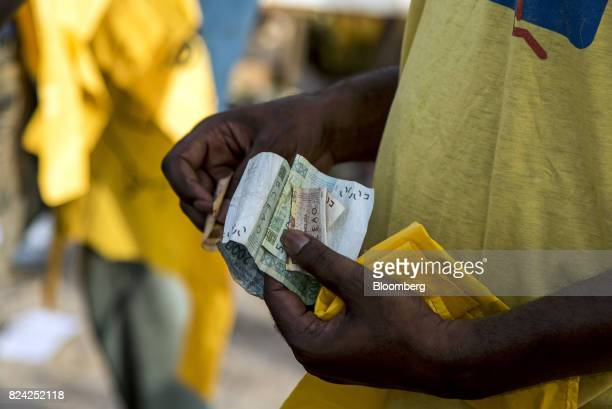 A customer holds West African CFA franc currency banknotes at the Soumbedioune fish market in Dakar Senegal on Friday July 28 2017 Senegalese voters...