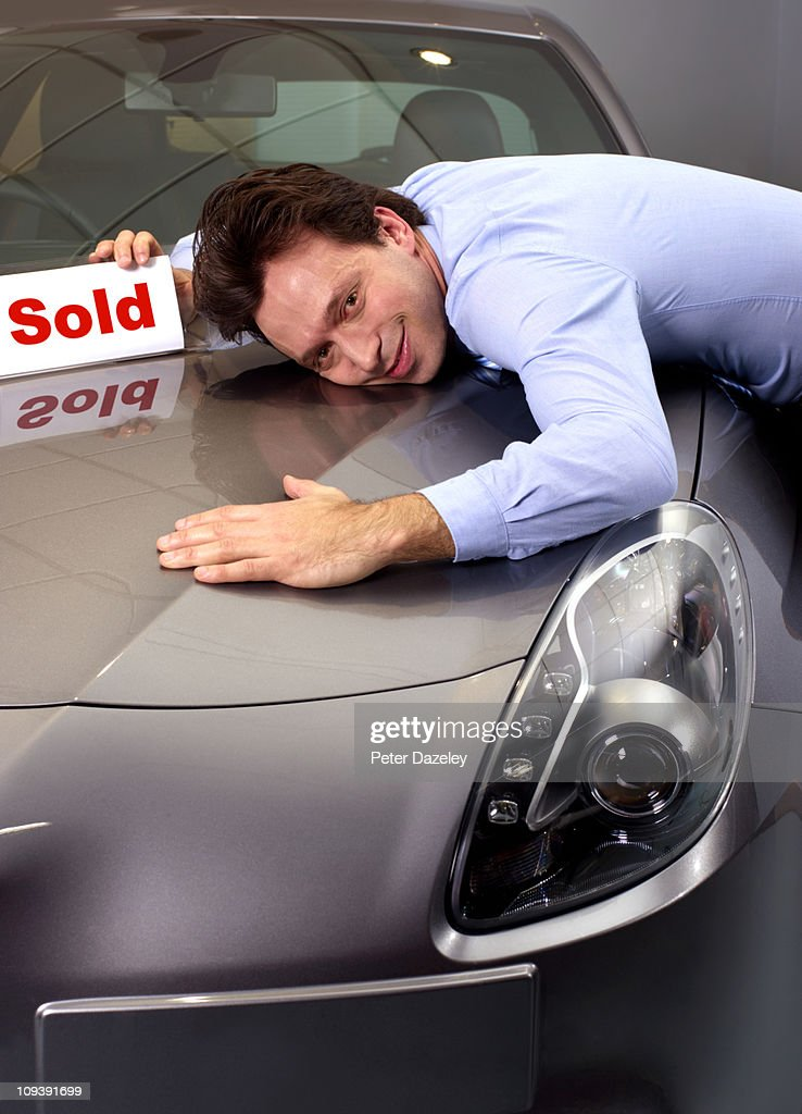 Customer hugging new car : Stock Photo