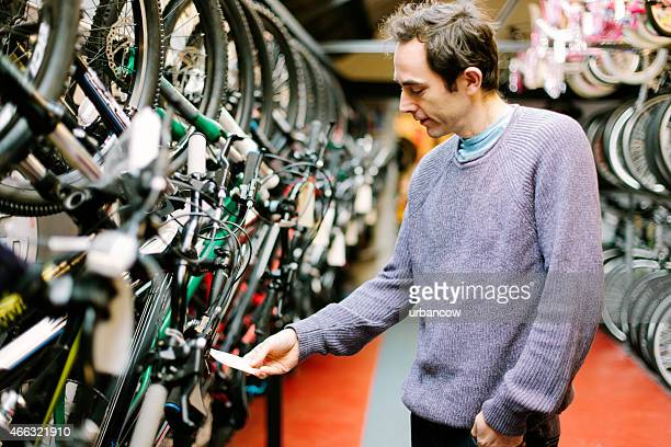 Customer in a bicycle shop, looking at the price tag