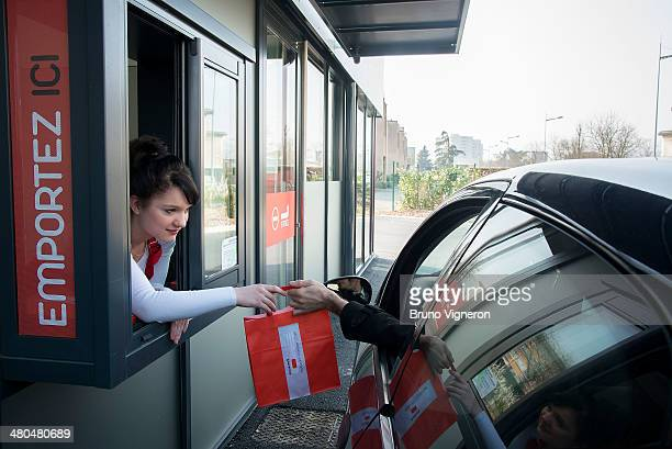 A customer in a car receives their order at the drivethru of Paul Bocuse's 'Ouest Express' fast food restaurant on March 13 2014 in...