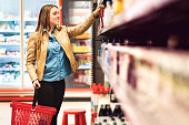 Customer in alcohol or drinks section in supermarket or liquor store holding a bottle from the shelf. Happy lady with shopping basket choosing alcoholic beverages. Woman buying groceries.