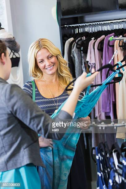 Customer in clothing store talking with saleswoman