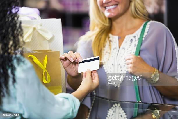 Il cliente in negozio pagando cassiere con buono regalo