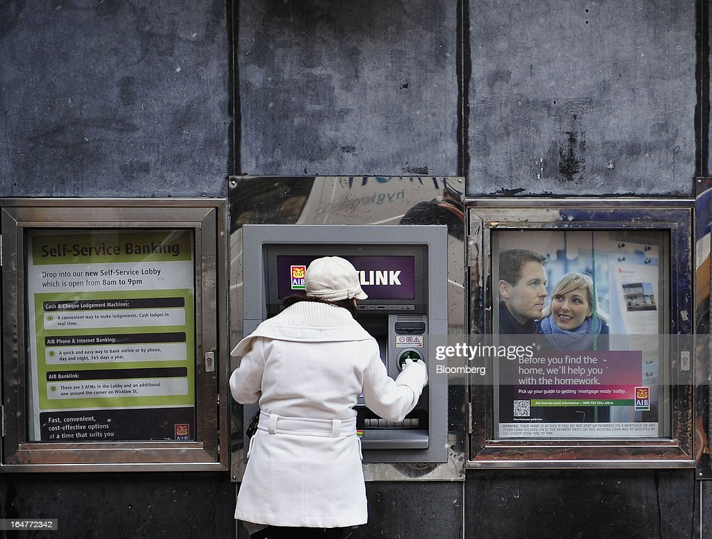 A customer inserts her bank card into an automated teller machine (ATM) outside an Allied Irish Banks Plc (AIB) branch on Grafton Street in Dublin, Ireland, on Wednesday, March 27, 2013. Allied Irish Banks Plc, which cost taxpayers about 21 billion euros ($27 billion) to rescue, said its annual loss widened as a decline in bad loan losses failed to offset dwindling gains from buying back its own debt. Photographer: Aidan Crawley/Bloomberg via Getty Images