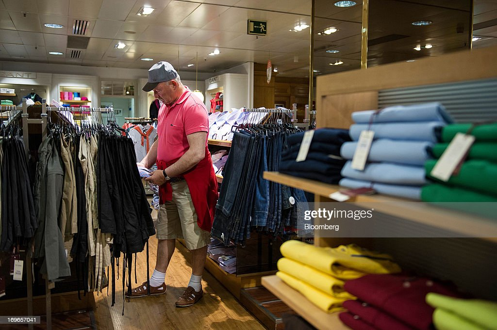A customer inspect men's clothing for sale inside an El Corte Ingles SA department store in Barcelona, Spain, on Thursday, May 30, 2013. Spain's recession eased in the first quarter as domestic demand stabilized while exports, which the government says will drive the recovery of the euro-area's fourth-largest economy, fell at the fastest pace in a year. Photographer: David Ramos/Bloomberg via Getty Images