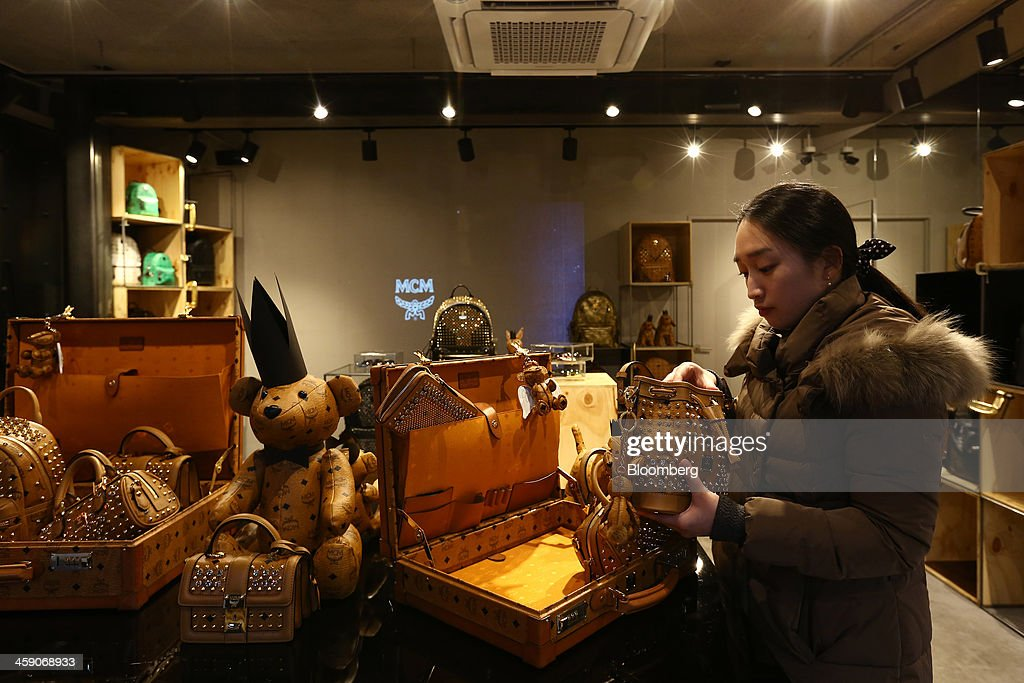 A customer inspects a bag inside an MCM Holdings AG store on Garosugil street in the Gangnam district of Seoul, South Korea, on Sunday, Dec. 22, 2013. Consumer prices climbed 0.9 percent in November from a year earlier after a 0.7 percent increase in October that was the smallest gain since July 1999. Photographer: SeongJoon Cho/Bloomberg via Getty Images